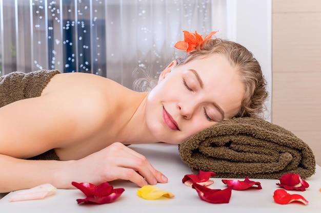 Jovem garota bonita feliz no salão spa relaxante em uma mesa de massagem. retrato de beleza