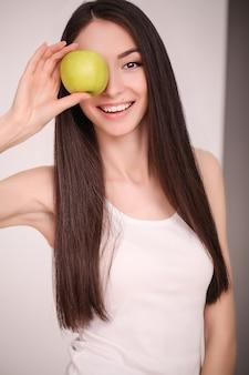 Jovem garota bonita que se importa com sua figura, fazendo escolhas alimentares saudáveis, frutas frescas.