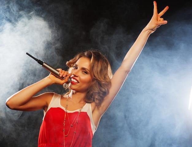 Jovem garota cantando no microfone na festa