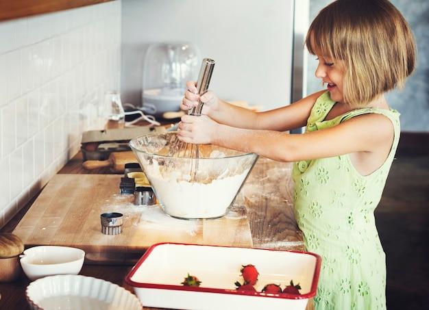 Jovem garota caucasiana com as mãos misturando massa de biscoito em uma tigela