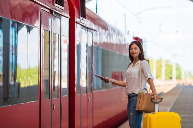Jovem garota caucasiana com bagagem na estação viajando de trem