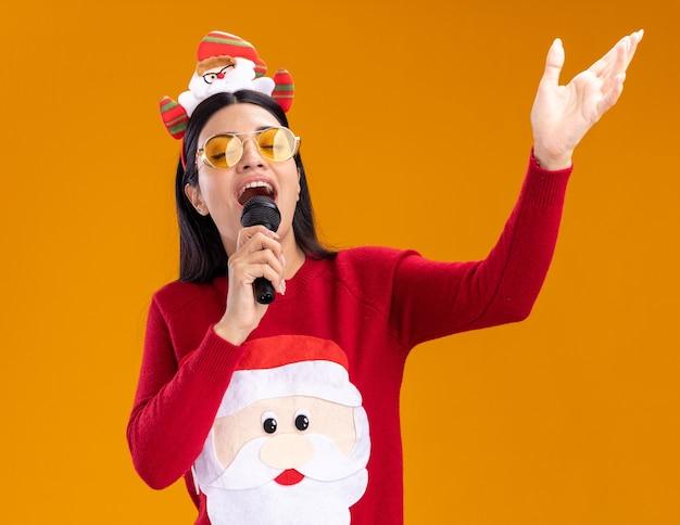 Jovem garota caucasiana com bandana de papai noel e suéter com óculos segurando o microfone perto da boca cantando com os olhos fechados, mantendo as mãos no ar isolado em fundo laranja