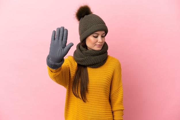 Jovem garota caucasiana com chapéu de inverno isolada em um fundo rosa fazendo gesto de pare e decepcionada