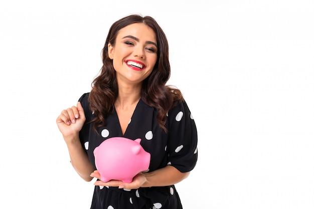 Jovem garota caucasiana com sorriso encantador, em vestido preto e branco em ervilhas detém um mealheiro de porco rosa e sorrisos, imagens isoladas na parede branca