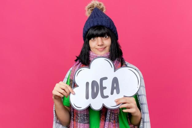 Jovem garota caucasiana doente e impressionada com chapéu de inverno e lenço embrulhado em xadrez segurando uma bolha de ideia isolada na parede vermelha com espaço de cópia