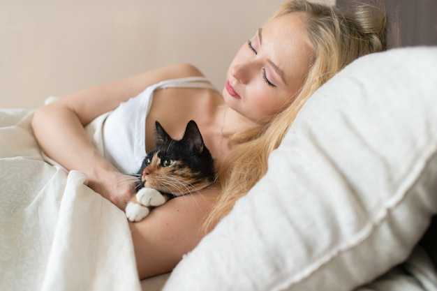 Jovem garota caucasiana dormindo na cama com um gatinho adorável.