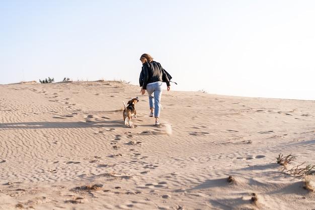 Jovem garota caucasiana em algum lugar em uma jaqueta de couro e jeans azul corre ao longo da praia com seu cachorro beagle amizade entre um cão e um homem. atividade de fim de semana emoções positivas