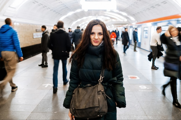 Jovem garota caucasiana em uma estação de metro e uma multidão de pessoas que se deslocam com blur