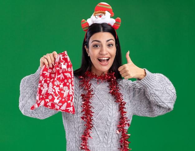 Jovem garota caucasiana impressionada com bandana de papai noel e guirlanda de ouropel no pescoço segurando um saco de presente de natal, olhando para a câmera, mostrando o polegar isolado no fundo verde