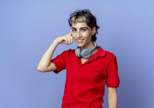 Jovem garota caucasiana sorridente com corte de cabelo de duende usando fones de ouvido no pescoço, colocando o dedo na têmpora isolado em um fundo roxo com espaço de cópia