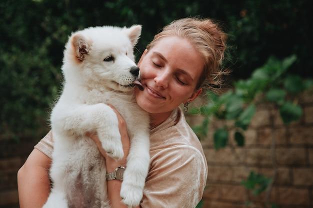 Jovem garota caucasiana sorridente segurando um samoiedo siberiano branco lambendo as bochechas.