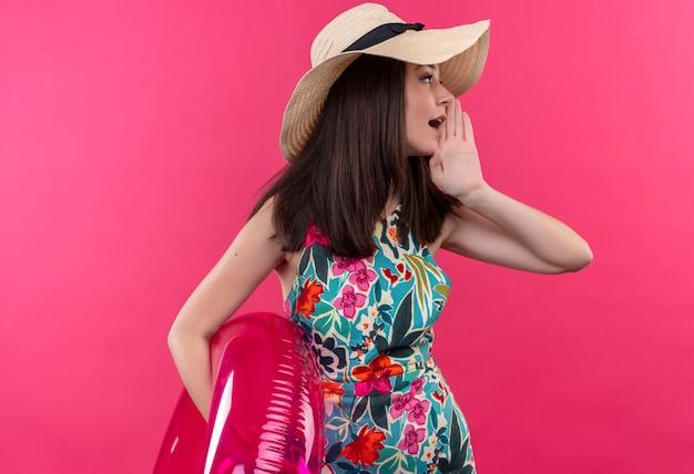 Jovem garota caucasiana sussurrando, usando um chapéu, segurando um anel de natação e segurando a mão perto da boca em um fundo rosa isolado