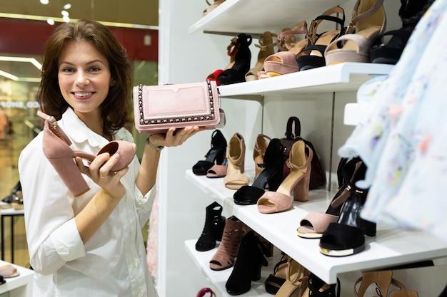 Jovem garota caucasin escolhe entre sapatos e clatch e sorrisos