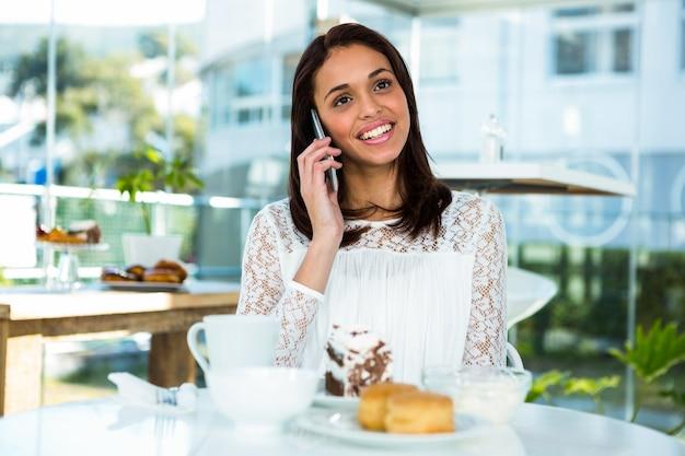 Jovem garota chamando tomando chá