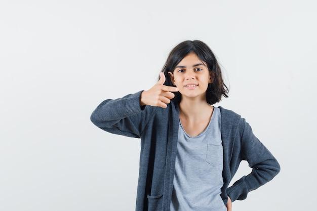 Jovem garota colocando uma mão na cintura, apontando para a direita com o dedo indicador em uma camiseta cinza claro e capuz cinza escuro com zíper frontal e está linda.