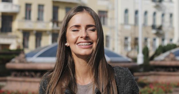 Jovem garota com aparelho nos dentes está sorrindo com os olhos fechados. retrato de mulher morena feliz de cabelos longos