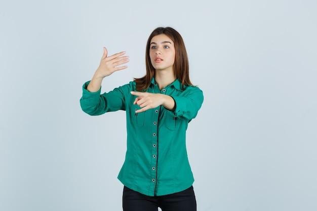 Jovem garota com blusa verde, calça preta, esticando a mão como segurando algo imaginário, mostrando o gesto de rock n roll e olhando com foco, vista frontal.
