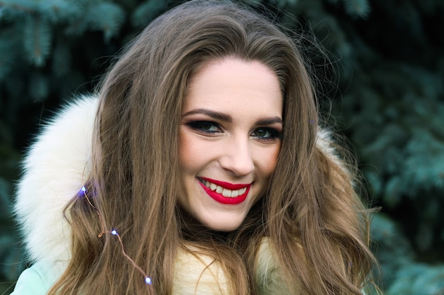 Jovem garota com cabelo cacheado castanho claro com maquiagem brilhante e lábios vermelhos com um sorriso.