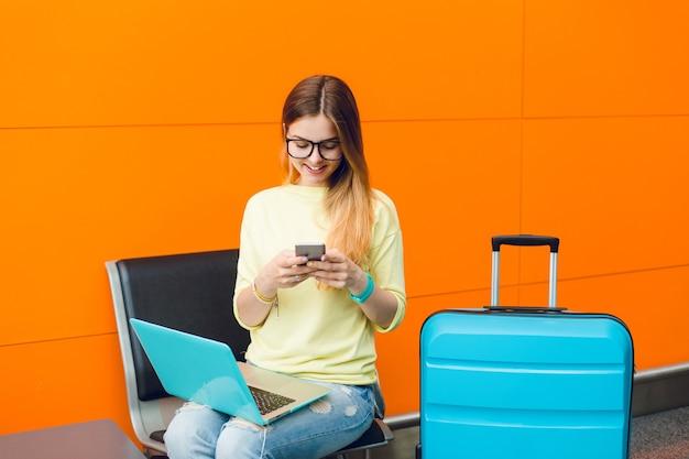 Jovem garota com cabelo comprido e óculos escuros está sentada na cadeira em fundo laranja. ela usa um suéter amarelo com jeans. ela tem laptop sobre os joelhos e mala perto. ela está digitando no telefone.