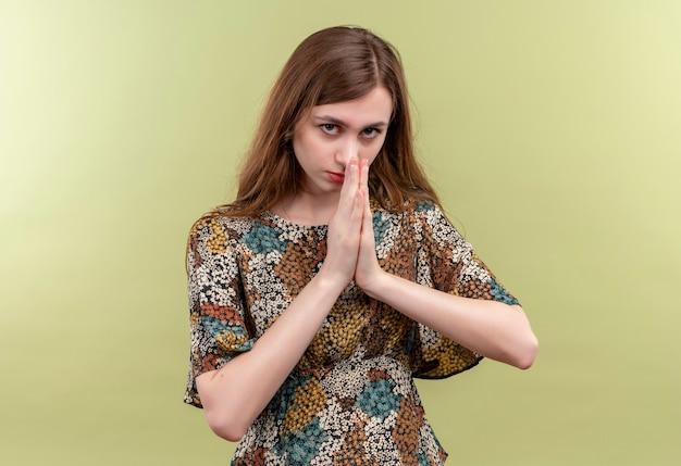 Jovem garota com cabelo comprido usando um vestido colorido de mãos dadas em gesto de oração namastê, sentindo-se grata e feliz