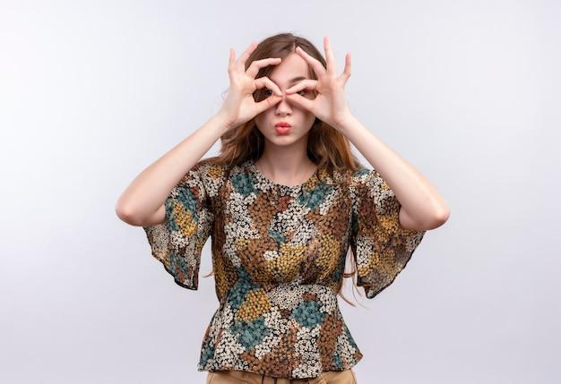 Jovem garota com cabelo comprido usando um vestido colorido fazendo sinais de ok com os dedos como binóculos olhando por entre os dedos