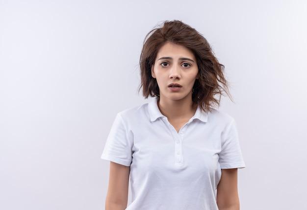 Jovem garota com cabelo curto e camisa pólo branca olhando para a câmera com uma expressão triste no rosto