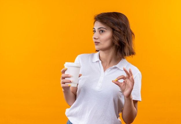 Jovem garota com cabelo curto e camisa pólo branca segurando a xícara de café sorrindo alegremente mostrando sinal de ok