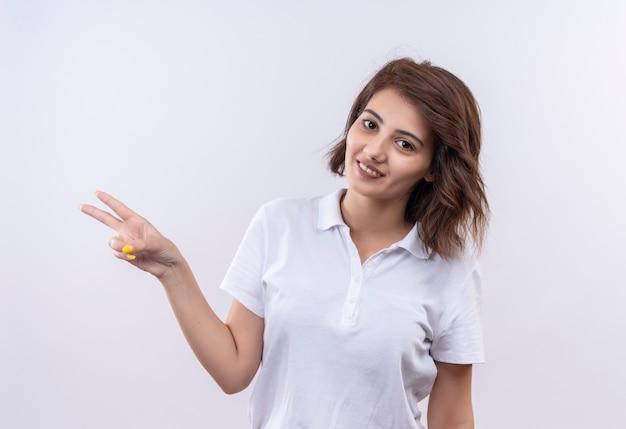 Jovem garota com cabelo curto e camisa pólo branca sorrindo alegremente mostrando sinal de vitória