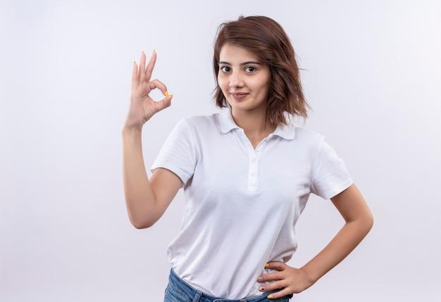 Jovem garota com cabelo curto e camisa pólo branca sorrindo confiante fazendo sinal de ok