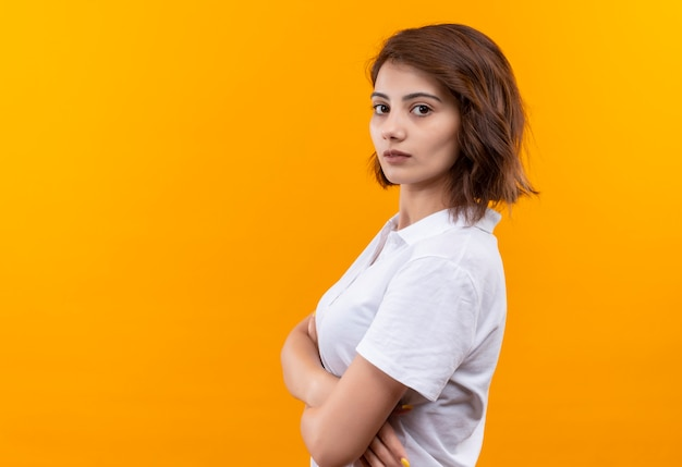 Jovem garota com cabelo curto e camisa pólo em pé de lado com os braços cruzados, olhando para a câmera com uma cara séria sobre fundo laranja