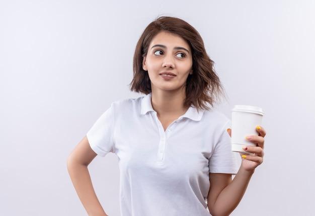 Jovem garota com cabelo curto usando uma camisa pólo branca segurando uma xícara de café sorrindo olhando para o lado