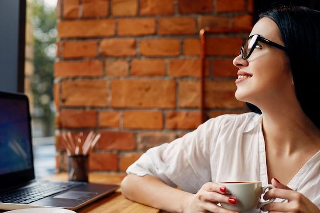 Jovem garota com cabelo preto, usando óculos, sentado no café com o laptop e uma xícara de café, conceito freelance, retrato, cópia espaço, camisa branca.
