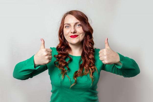 Jovem garota com cabelo vermelho e batom vermelho, mostrando os polegares ou como no fundo da parede cinza
