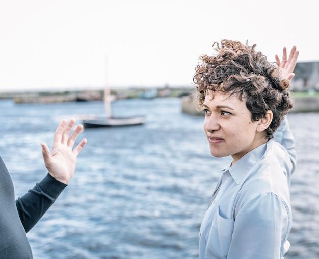 Jovem garota com cabelos cacheados e um nariz penetrante, discutindo com seu parceiro com gestos expressivos com o mar fora de foco