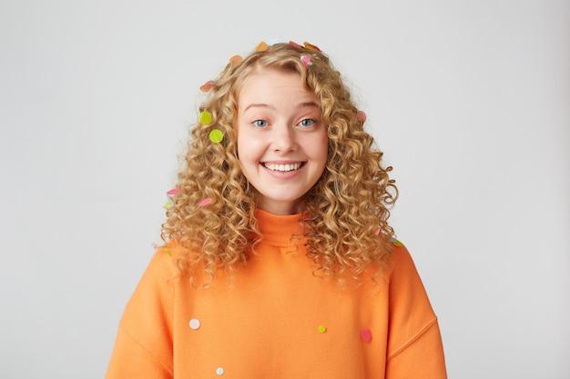 Jovem garota com cabelos loiros e olhos azuis sorrindo mostra dentes saudáveis, olha um pouco surpresa