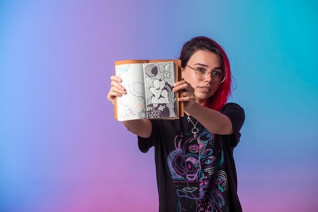 Jovem garota com cabelos rosa segurando um caderno de desenho e demonstrando-o.