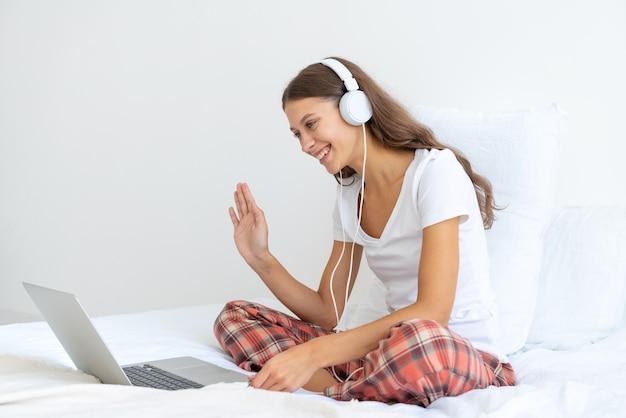 Jovem garota com fones de ouvido falando em teleconferências, acenando com a mão, sorrindo.