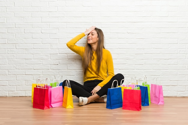Jovem garota com muitas sacolas de compras acaba de perceber algo e pretende a solução
