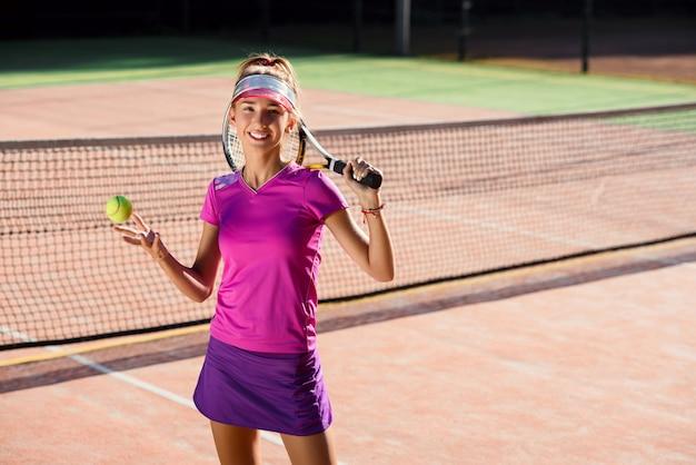 Jovem garota com o uniforme de tênis elegante vomitando bola de tênis e pegá-lo na mão no fundo da quadra ao ar livre.