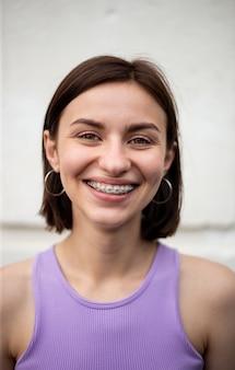 Jovem garota com penteado bob e camiseta puðºple sorrindo com aparelho dentário de metal para correção de mordida nos dentes