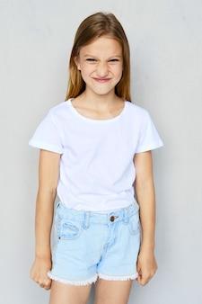 Jovem garota com raiva em shorts brancos de camiseta e calça jeans posando no estúdio