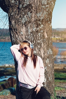 Jovem garota com roupas casuais, usando seus fones de ouvido e telefone celular para ouvir música.