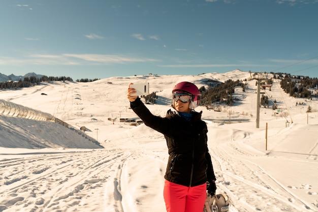 Jovem garota com roupas de esqui, um par de óculos de proteção e um capacete de esqui fazendo uma selfie em uma estação de esqui