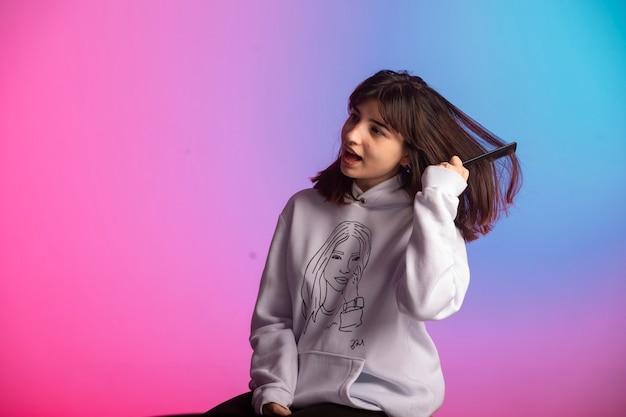 Jovem garota com roupas esportivas, escovando os cabelos e se machuca.