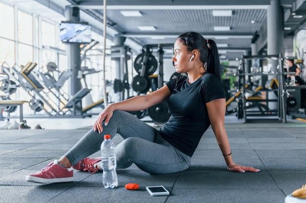 Jovem garota com roupas esportivas, fazendo uma pausa com comida e água está no ginásio durante o dia.