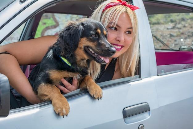 Jovem garota com seu cachorro no carro viajando nas férias de verão.