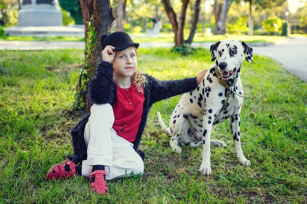 Jovem garota com seus cães dálmatas em um parque primavera.