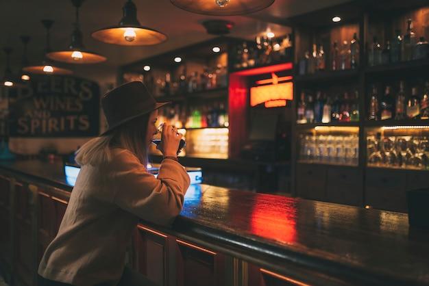 Jovem garota com um suéter marrom claro e um chapéu marrom escuro, tomando um refrigerante em um bar