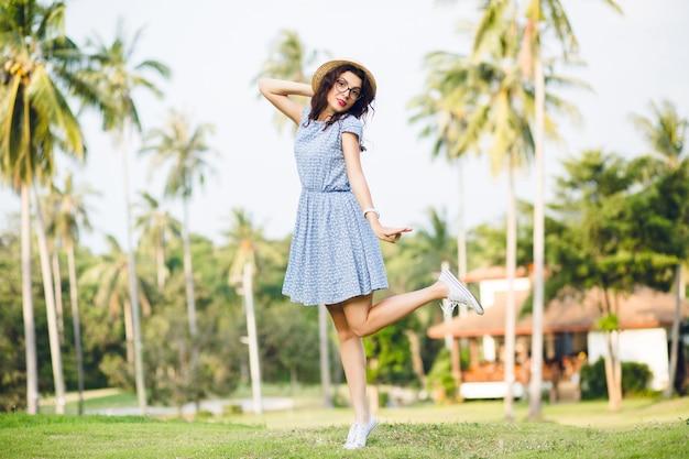 Jovem garota com um vestido azul-celeste está de pé em uma perna na ponta dos pés em um parque. menina com chapéu de palha e óculos escuros.