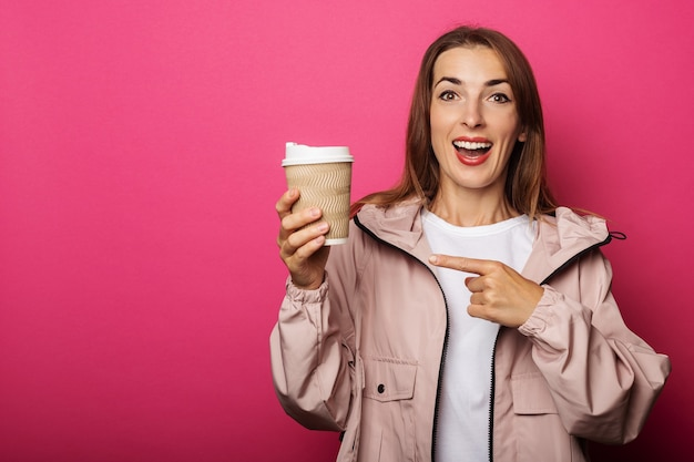 Jovem garota com uma jaqueta segura uma folha de papel e aponta para ela com um dedo em uma superfície rosa